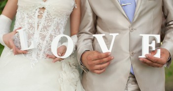 Closeup shot of bride and groom hands holding the word Love