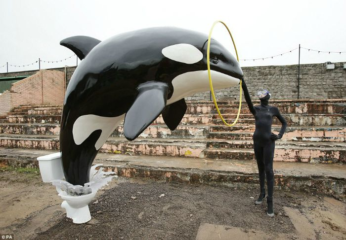 Sculpture showing killer whale jumping out of toilet at Banksy's Dismaland